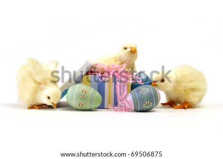 A few chicks isolated on white with some easter eggs. - stock photo