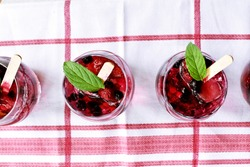 A few glasses full of forged berries in sparkling water stand on a surface - delicious, healthy and sweet refreshment for the summer - delicious wild berries in water as soothing refreshment