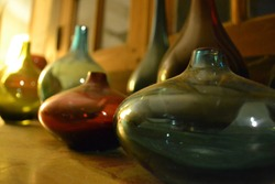 A few old colorful jars filled with liquid on a wooden table  with a blurry background