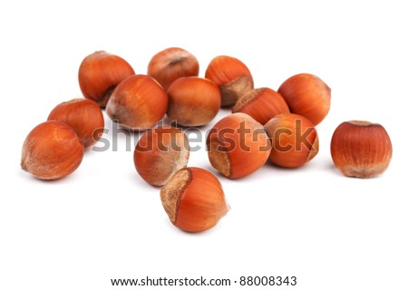 A few ripe hazelnuts on a white background