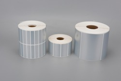 A few rolls of silver thermal print label paper