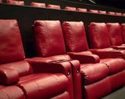 A few rows of recliner movie theater seats in a luxury movie theater