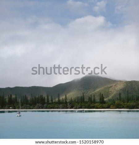 A few small boats at Kuto Bay beach with Pic N'Ga Mountain engulfed in clouds in the background and Pine trees in foreground on Isle of Pines in New Caledonia Archipelago in South Pacific Ocean.
