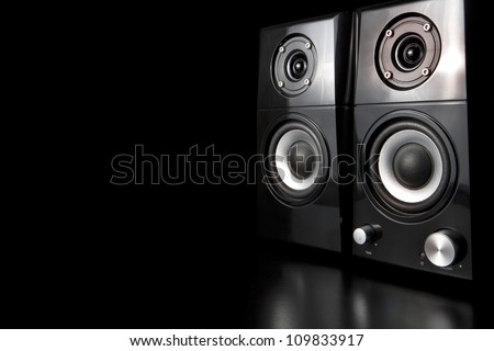 A few speakers on a black background.