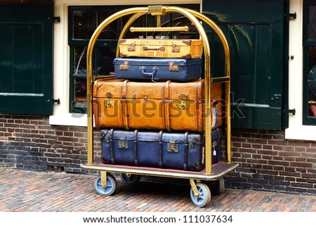 A few vintage suitcases on a trolley.
