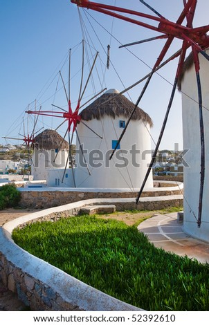 A few windmills on the island of Mykonos, surrounded by grass and the blue sky