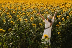 A field of sunflowers. Beautiful Girl in a white dress and a straw cap among many blooming sunflowers enjoying the nature and view. Gorgeous girl enjoying bright nature and sunflowers on a sunny day.