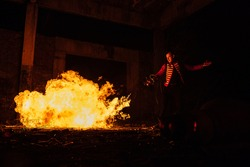 a fiery performance by a professional fireshow artist, a dangerous art of control with a hot bright flame escaping from a flamethrower, a spectacular bright show in the dark
