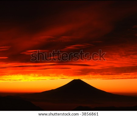 A fiery sunrise over the silhouette of sacred Fuji