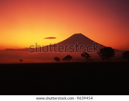 A fiery sunrise over the silhouette of sacred Fuji