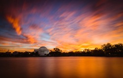 A fiery sunrise over the Tidal Basin in Washington DC featuring the Jefferson Memorial.