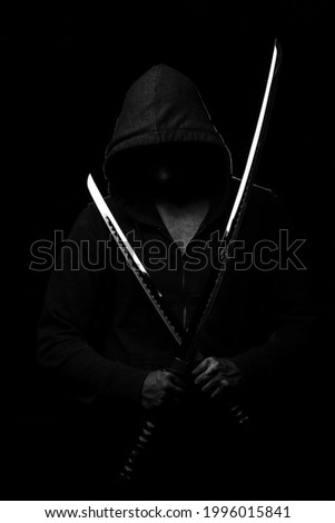A fighter in black clothes with a hood on his head holds two sparkling Japanese swords on a black background Foto stock ©