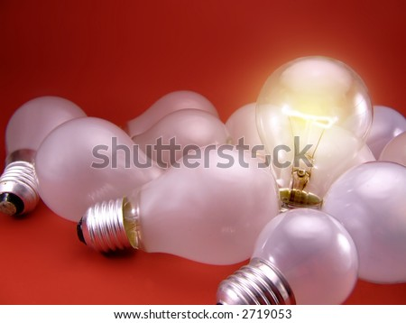 A figurative picture of light bulbs. Dull white lamps (off) with one bright, clear burning bulb. Representing one bright mind/idea in a crowd