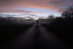 A figure back to camera on a road heading into the sunset on a moody atmospheric winters evening.