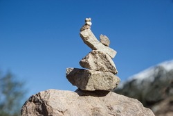 A figure of stones against the background of a clear sky. Stone pyramid.