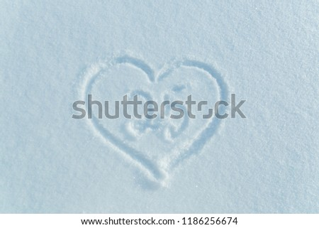A figure of twenty five written in the snow in the painted heart. Snow texture. #1186256674
