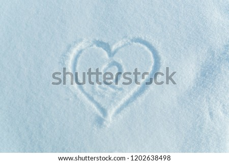 A figure of two written in the snow in the painted heart. Snow texture. #1202638498