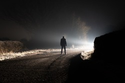 A figure standing on a road. Looking at a bright light round a corner. On a spooky country lane. On a misty winters night.