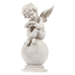 A figurine of a tired little angel from a gypsum resting on a round stone. On isolated white background