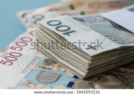 a file of Polish banknotes of one hundred zlotys fastened with a bank band lying on the money with the highest denomination five hundred zlotys