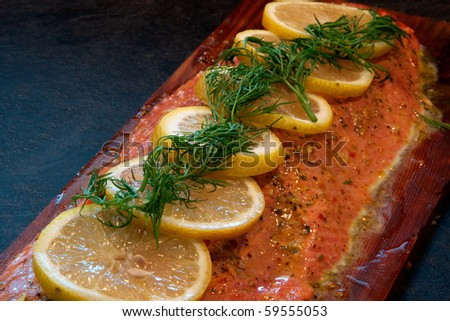 A fillet of sockeye salmon with dill and lemon on cedar plank