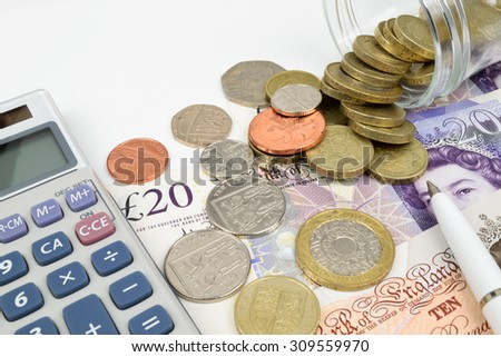 A finance still life with a jar of Sterling coins on Sterling notes, calculator and pen.