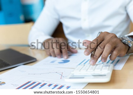 A financial businessman, a young man analyzes financial data using a computer and calculator to compute and summarize the data in a graph to propose to the president.