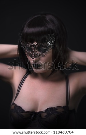 A fine art nude portrait of a young woman wearing a black venetian mask