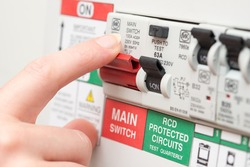 A finger is about to switch off a large red MAINS switch on an RCD circuit breaker board