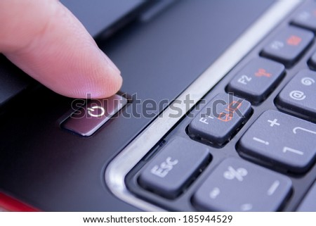 a finger is pushing the power button to wake laptop up or shutdown it
