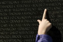 a finger points out a name inscribed at the Vietnam Veterans Memorial in Washington, DC