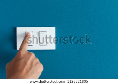 A finger turning on lighting switch on rough on blue dark wall. Empty space for text your