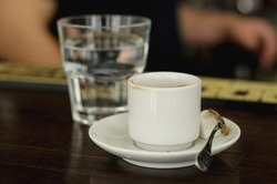 a finished white cup of coffee with a white saucer and spoon on the blurred background of a glass glass with water