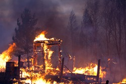 A fire destroys a charred burnt house against a background of trees. Charred in flame house at night. Fire everywhere and smoke in a residential area at night. Dangerous fire.Window of a house on fire