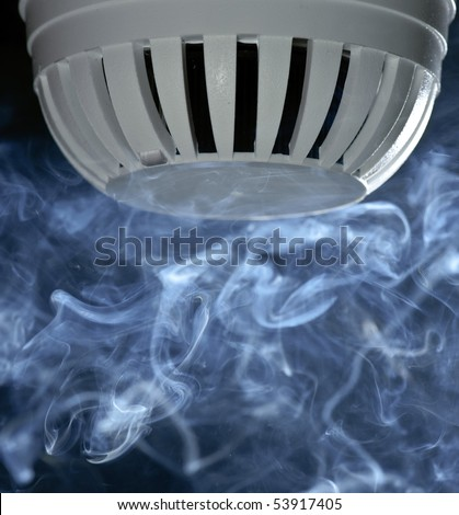 A fire detector with smoke rising.