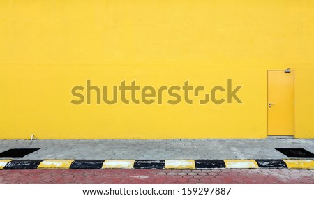 A fire escape door on a blank yellow color sidewall of a building.