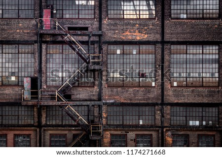 A fire escape on an old brick building in urban landscape. #1174271668