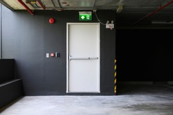 A fire exit with the sign and red alarm bell above the white door on the parking building.