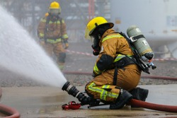 A fire fighter is controlling a fire monitor in order to combat fire. Visible water mist in the background.