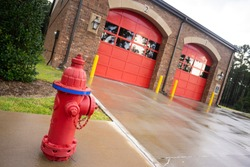 A fire hydrant stands outside the two bay garage that serve as the fire department truck protection