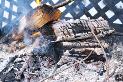 A fire in a caged metal fireplace burns outdoors, with white, glowing hot embers of the coal from burning wood. Smoke rises from the charred logs and branches.