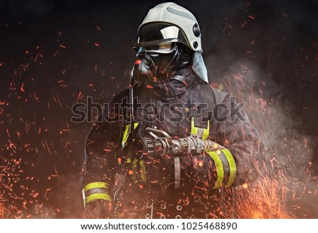 A firefighter dressed in a uniform in a studio. Stock photo ©