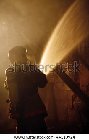 A Firefighter fighting a fire. Nighttime