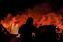 A firefighter in combat uniform puts out a dangerous fire in the city. The concept of disaster