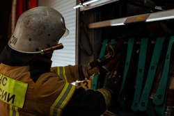 A firefighter in uniform and helmet pulls a fire hose out of a fire brigade vehicle. The concept of extinguishing fires and the work of emergency services.