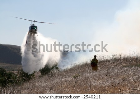 A firefighter watches as a helicopter drops water on a brush fire