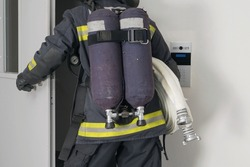 a firefighter with equipment for extinguishing fires enters the iron door