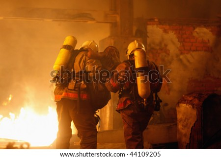 A firefighters carrying an accident victim from a fire