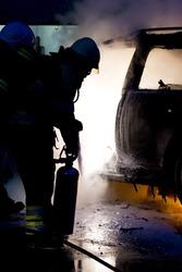 A fireman extinguishes a car-fire