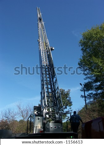 A firetruck ladder that is fully extended into the blue sky.  There is a fireman climbing near the top.